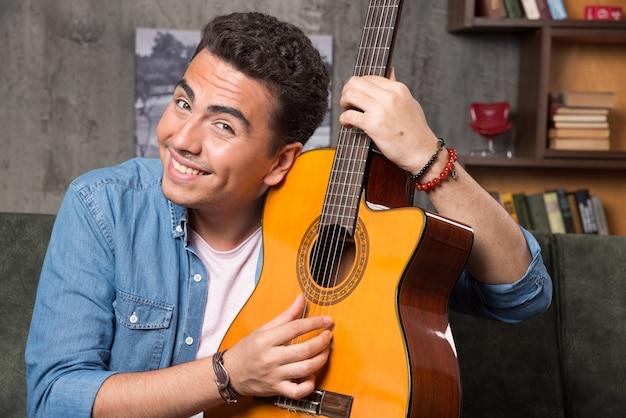 Wesoły człowiek pokazuje piękną gitarę i siedzi na kanapie. wysokiej jakości zdjęcie