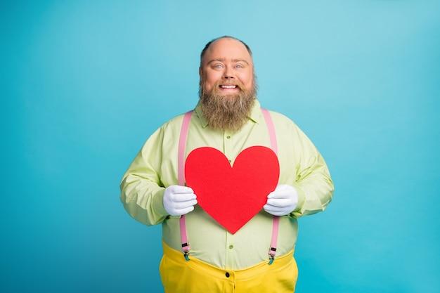 Wesoły człowiek trzyma wielkie serce karty walentynkowej na niebieskim tle