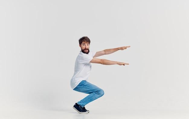 Wesoły człowiek w biały t-shirt i dżinsy studio ubrań na białym tle. wysokiej jakości zdjęcie