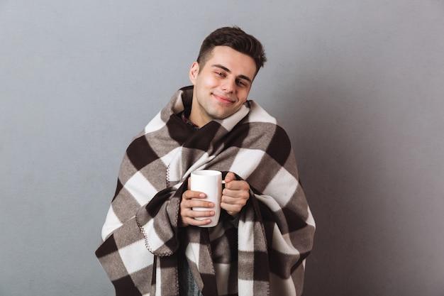 Wesoły człowiek w ciepłej kratki, trzymając gorącą herbatę
