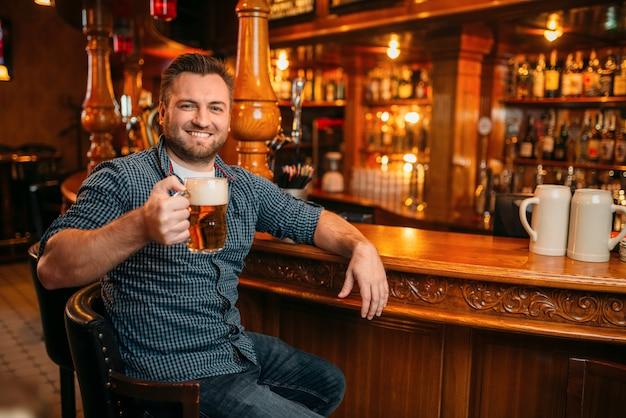 Wesoły człowiek z kuflem piwa przy kasie w pubie. brodaty mężczyzna ze szklanką alkoholu, zabawy w barze