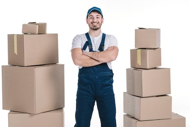 Wesoły deliveryman między stertami paczek