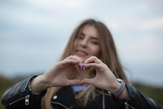 Wesoły długowłosy model przedstawiający symbol serca z dwiema rękami na tle miasta. miejsce na tekst