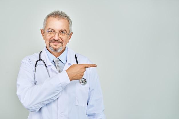 Wesoły dojrzały lekarz pozowanie i uśmiechnięty