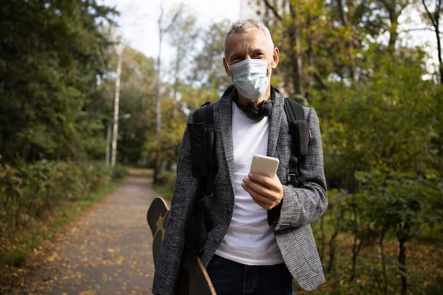 Wesoły dojrzały mężczyzna w masce spacerujący ze smartfonem w drewnie