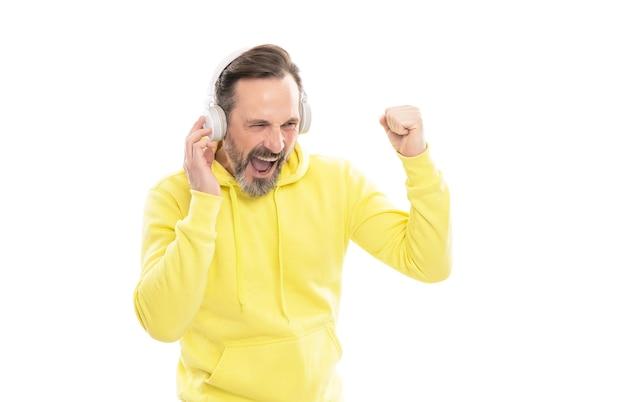 Wesoły dojrzały mężczyzna z brodą i wąsami w bluzie z kapturem słuchać muzyki lub książki audio w słuchawkach na białym tle, muzyka.