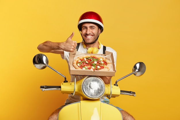 Wesoły doręczyciel w kasku prowadzący żółtą hulajnogę, trzymając pudełko po pizzy