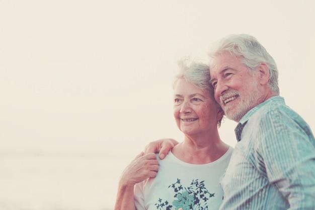 Wesoły dorośli uśmiechający się i kochający się - koncepcja wakacji, turystyki, podróży i ludzi - szczęśliwa para starszych na kamienistej plaży śmiać się i żartować, przytulając się nawzajem. białe włosy i srebrne społeczeństwo