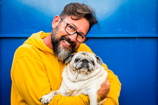 Wesoły dorosły mężczyzna uśmiecha się i przytula z miłością swojego starego psa mopsa w portrecie w kolorze żółtym i niebieskim - ludzie ze zwierzętami i okularami cieszą się koncepcją terapii dla zwierząt