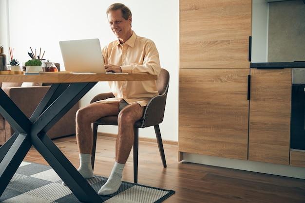 Wesoły dorosły mężczyzna utrzymujący uśmiech na twarzy podczas pracy na odległość przy swoim komputerze w domu