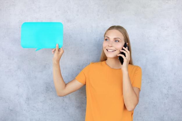 Wesoły dorywczo młoda kobieta na białym tle nad szarym tłem, rozmawia przez telefon komórkowy, pokazując pusty dymek.