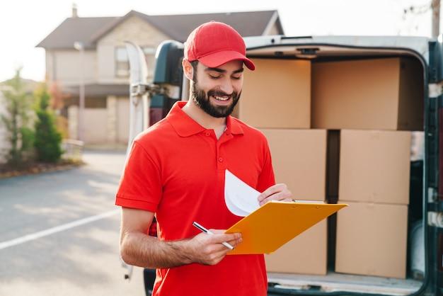 Wesoły dostawca w czerwonym mundurze trzymający schowek i piszący w pobliżu samochodu z paczkami na zewnątrz