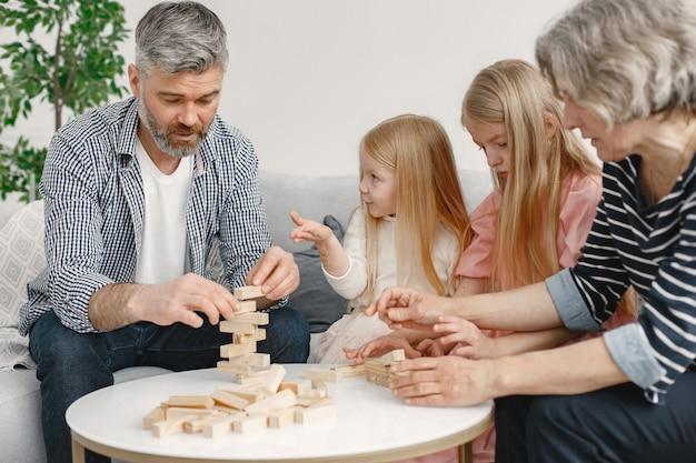 Wesoły dziadkowie i wnuki razem grają w klocki z drewnianą wieżą. wnętrze salonu.