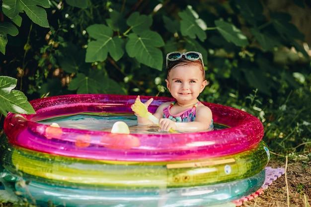 Wesoły dziecko cieszy się jej dzień w sumer w jej basenie trzymając plastikową łyżkę