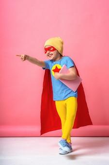 Wesoły dziecko ubrane w kostium superbohatera i kapelusz z książką w ręku.