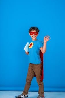 Wesoły dziecko ubrane w kostium superbohatera trzyma książkę i fale.