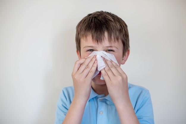 Wesoły dziecko wyciera nos białą chusteczką. higiena nosa. dziecko z grypą lub przeziębieniem chronione przed wirusami wśród pacjentów z koronawirusem