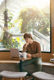 Wesoły dziennikarz płci męskiej w modnych okularach z przyjemnością kończy pracę nad recenzją książki, czytając ją ponownie w tekście zeszytu, zanim zadzwoni do redakcji, aby przedstawić publikację, pijąc kawę na lunch w kawiarni