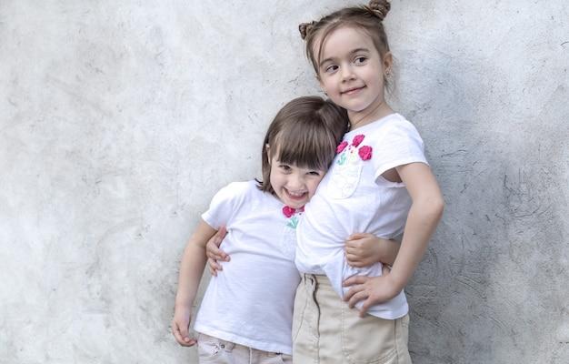 Wesoły dziewczynki na szarym tle z teksturą. zewnątrz portret dziewczynki. szare tło z teksturą ściany.