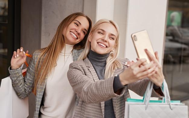 Wesoły dziewczyny biorąc selfie po zakupach