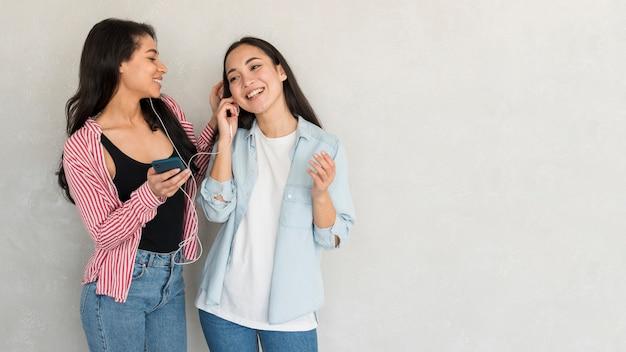 Wesoły dziewczyny słuchają muzyki w słuchawkach
