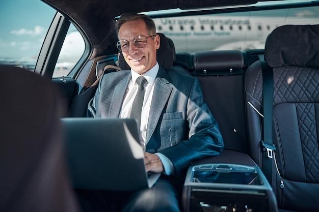 Wesoły elegancki mężczyzna w okularach siedzi w samochodzie z notebookiem podczas transferu na lotnisko