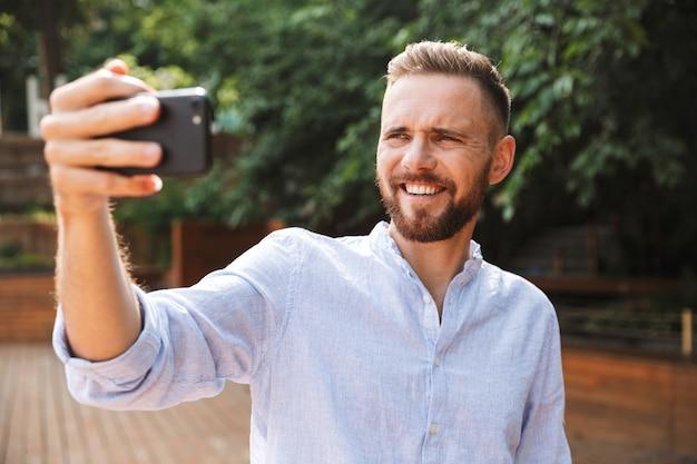 Wesoły emocjonalny młody brodaty mężczyzna wziąć selfie