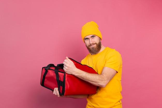 Wesoły europejski brodaty mężczyzna dostawy zaskoczony emocjami otwiera pudełko z jedzeniem na różowo