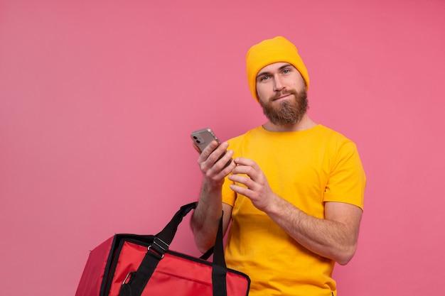 Wesoły europejski człowiek dostawy z torbą na co dzień trzymaj telefon na różowo