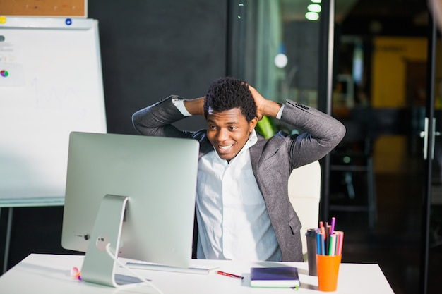 Wesoły facet człowiek wygląda szczęśliwie na monitorze przedsiębiorca pomyślny pracownik biurowy freelancer