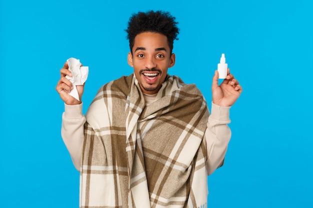 Wesoły facet czuje się lepiej po zastosowaniu przepisanego lekarza, nosząc koc jak zachorował, zachorował na grypę lub grypę, trzymając spray do nosa i pigułki z apteki, uśmiechnięty, niebieska ściana