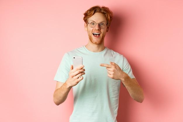 Wesoły facet opowiada o promocji internetowej, uśmiechając się zdumiony i wskazując palcem na smartfona, stojąc na różowym tle.
