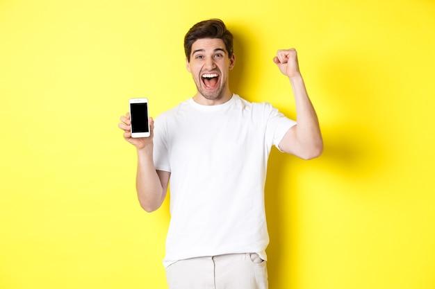 Wesoły facet pokazujący ekran smartfona, podnoszący rękę do góry i świętujący, triumfujący nad osiągnięciem internetowym, stojący na żółtym tle