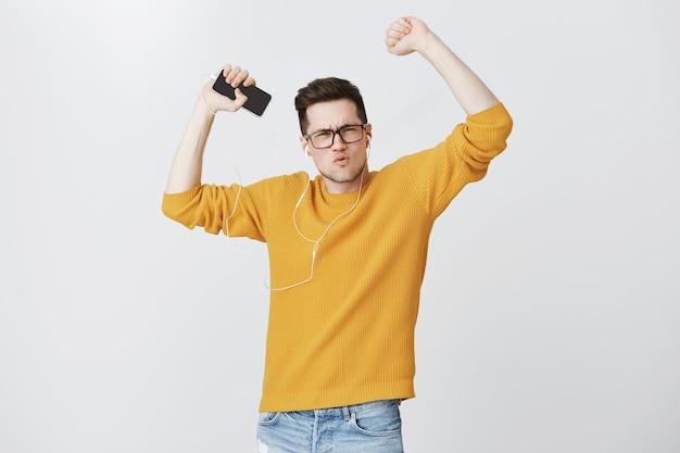 Wesoły facet tańczy z podniesionymi rękami, słuchając muzyki w słuchawkach