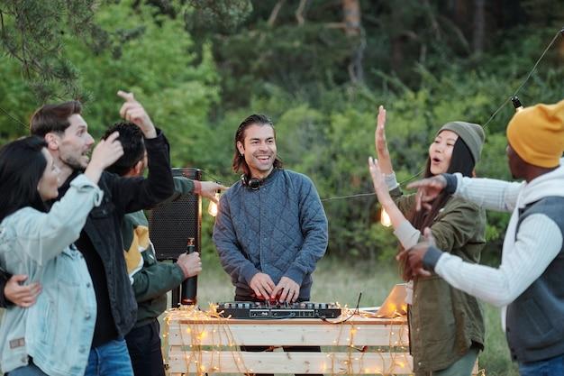 Wesoły facet w kurtce i słuchawkach robi muzykę przed tańczącym tłumem, ciesząc się letnim weekendem w naturalnym środowisku