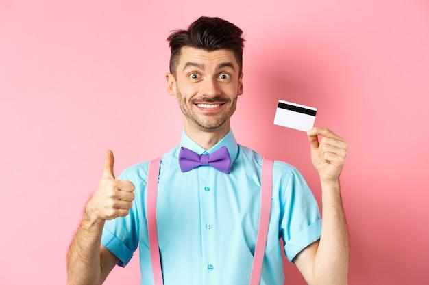 Wesoły facet w muszce pokazujący kciuk do góry i plastikową kartę kredytową, jak oferta promocyjna, uśmiechnięty szczęśliwy do kamery, stojący na różowym tle.