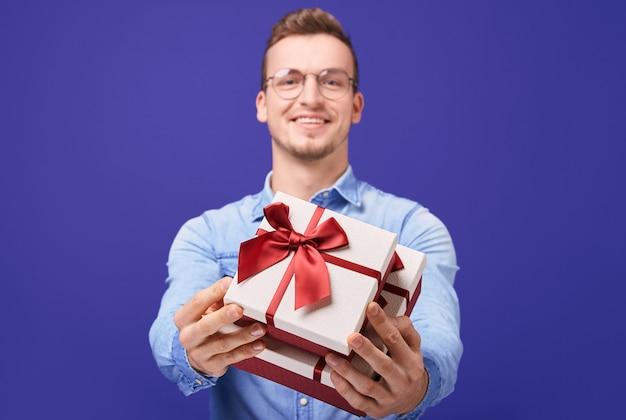 Wesoły facet w niebieskiej dżinsowej koszuli i okrągłych okularach daje ci prezent
