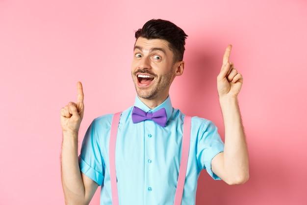 Wesoły facet z francuskimi wąsami, przedstawiający pomysł, tańczący i podnoszący palce w górę, mający rozwiązanie, stojący szczęśliwy na różowym tle.