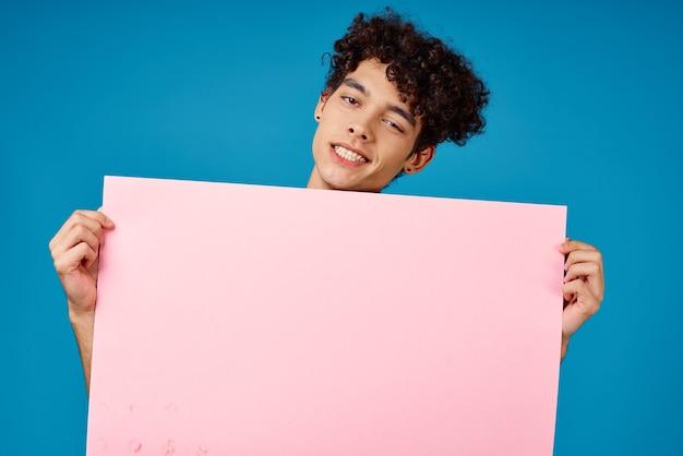 Wesoły facet z różowym plakatem makieta kopiuje miejsce na niebieskim tle