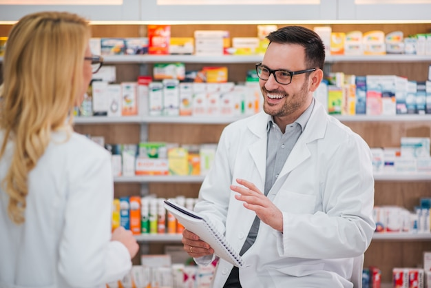 Wesoły farmaceuta rozmawia z jego koleżanką.