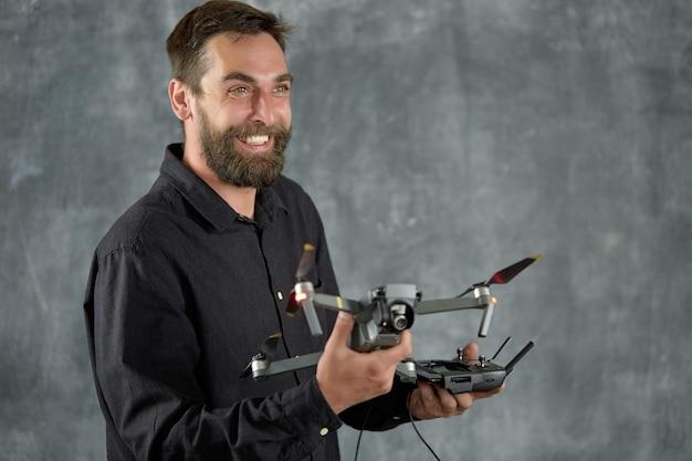 Wesoły filmowiec trzyma odległy bezzałogowy statek powietrzny z kamerą w ręku