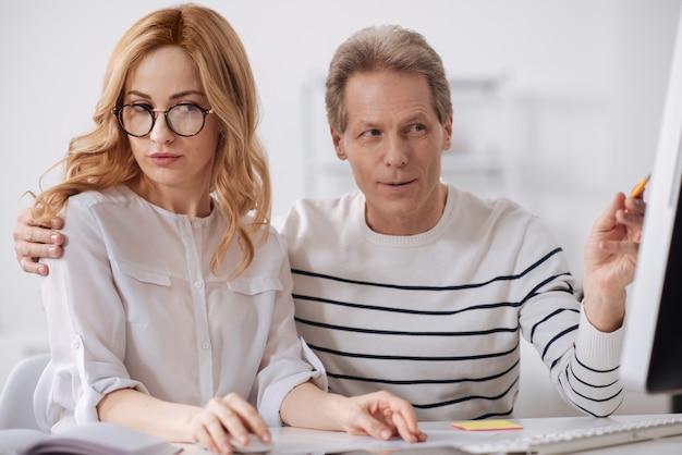 Wesoły flirtujący dojrzały biznesmen siedzi w biurze i pracuje nad projektem, flirtuje i dotyka młodej sekretarki