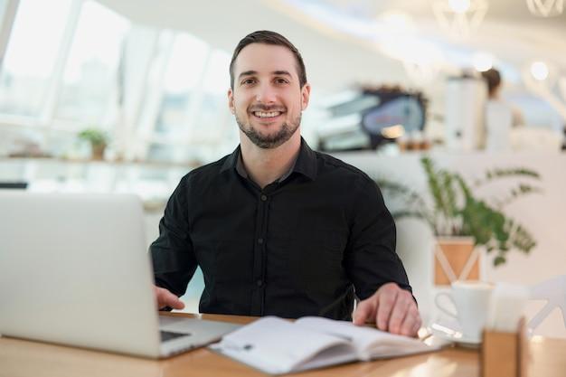 Wesoły freelancer człowiek pracujący z kawiarni. atrakcyjny młody człowiek uśmiechnięty, używając swojego nowoczesnego laptopa i patrząc na kamery. przytulna kawiarnia na tle. rozmazany otwarty pamiętnik, kubek kawy na stole.