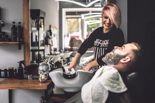 Wesoły fryzjer i klient przygotowuje się do leczenia