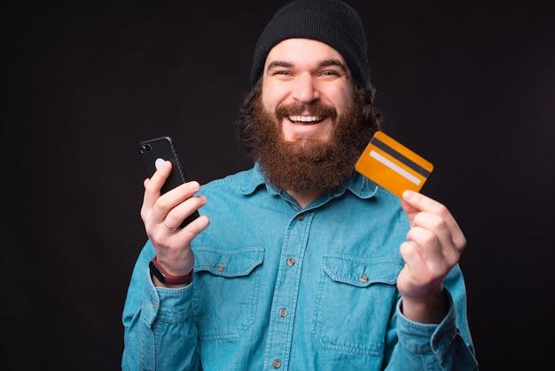 Wesoły hipster brodaty mężczyzna uśmiecha się i używa karty kredytowej i smartfona