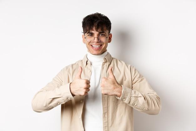 Wesoły hipster facet w okularach pokazujący kciuki do góry i uśmiechnięty, jak dobry produkt, polecam lub chwalę, stojąc na białej ścianie.