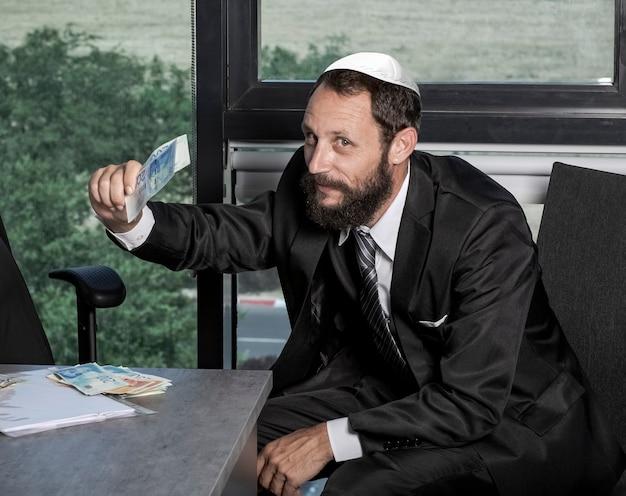 Wesoły i beztroski odnoszący sukcesy, bogaty kaukaski biznesmen w biurze rzucający pieniędzmi, bawiący się gotówką izraelskie banknoty nis, siedzący zadowolony z zadowolonej twarzy. pomysł na pieniądze i sukces.