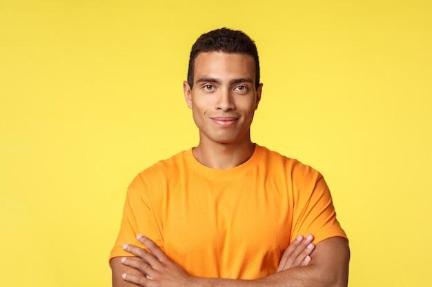 Wesoły i silny młody sportowiec mężczyzna w casual t-shirt, skrzyżowane ramiona