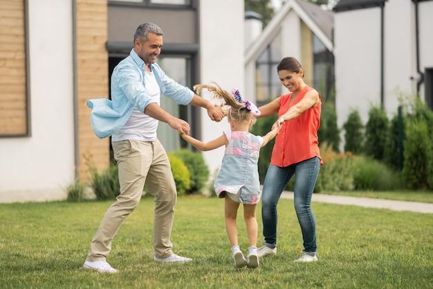 Wesoły i szczęśliwy. rodzina czuje się wesoła i szczęśliwa podczas zabawy na zewnątrz w pobliżu domu