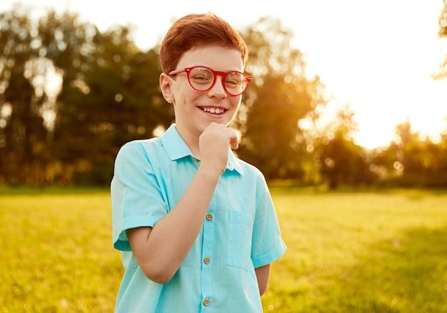 Wesoły, inteligentny uczeń w stroju casual i okularach, uśmiechający się i patrzący w kamerę, stojąc w zielonym parku w słoneczny letni dzień